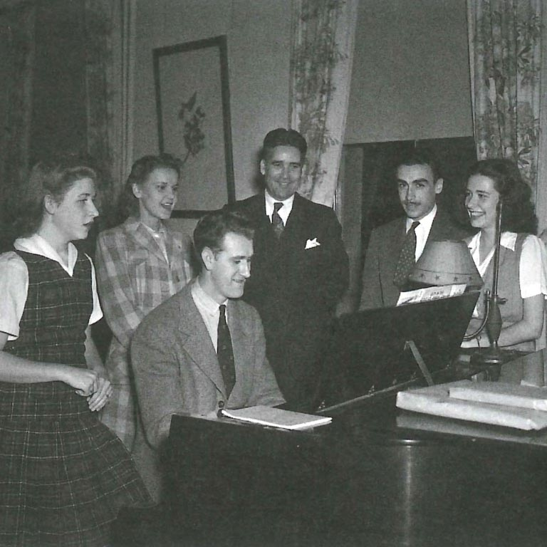 A historical photo of men and women gathered around a man playing the piano