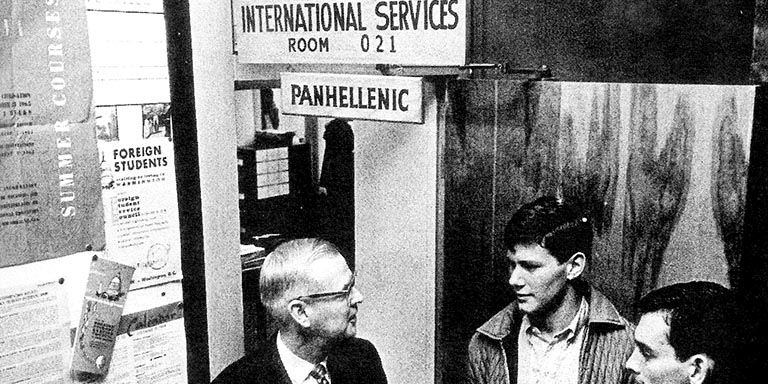 The dean and two students stand beneath a sign that reads, International Services Room 021.