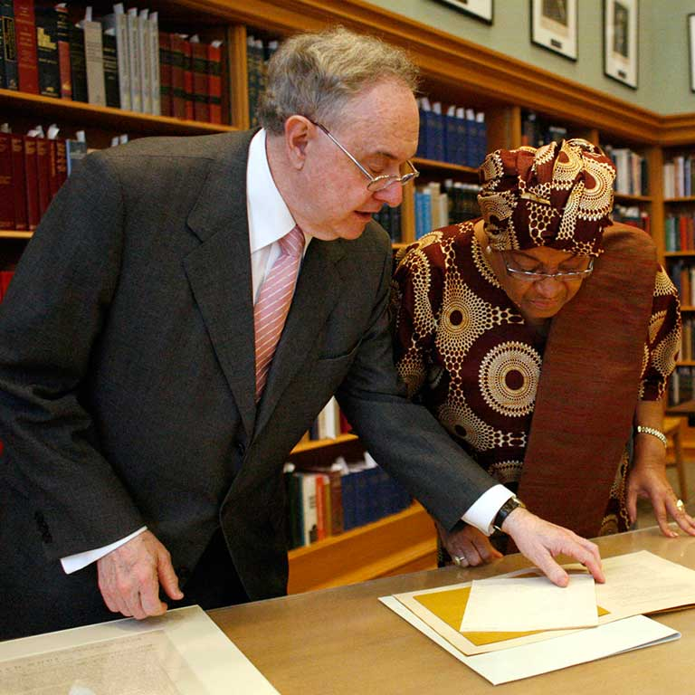 Patrick O'Meara and Ellen John Sirleaf examine a paper on a table.