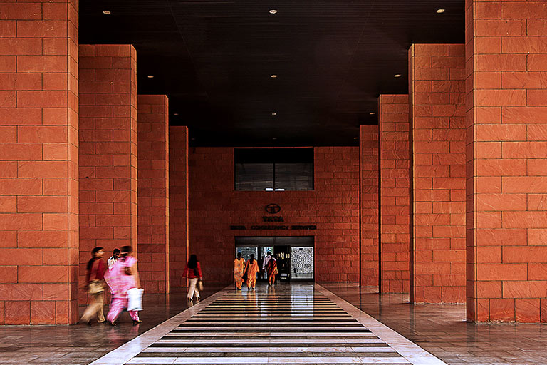 People walk down a long hall with tall brick columns on either side.