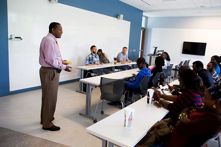 A faculty member lectures in front of a class.