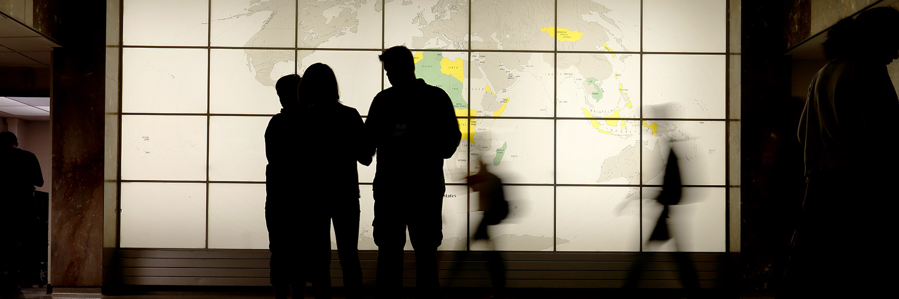 Three people are silhouetted in front of a world map.