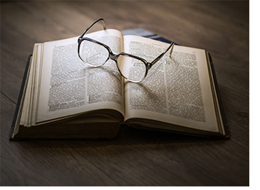 Open book with a pair of glasses on it.