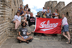 Students with an IU flag standing at the great wall of China.