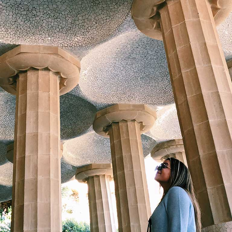 A woman looks at decorative columns.