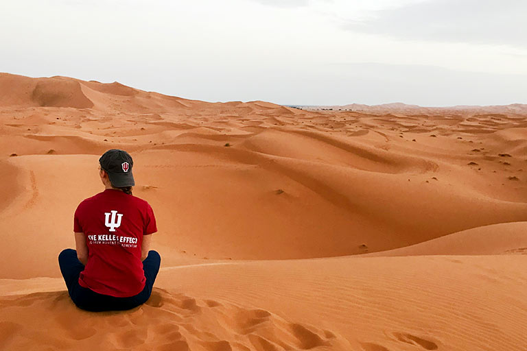 An IU Kelley School of Business student sits in a desert.