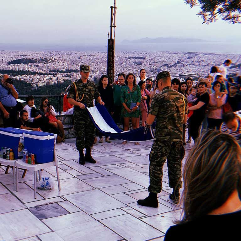 An audience watches as two soldiers fold a flag.